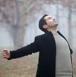 Man in woods taking deep breath