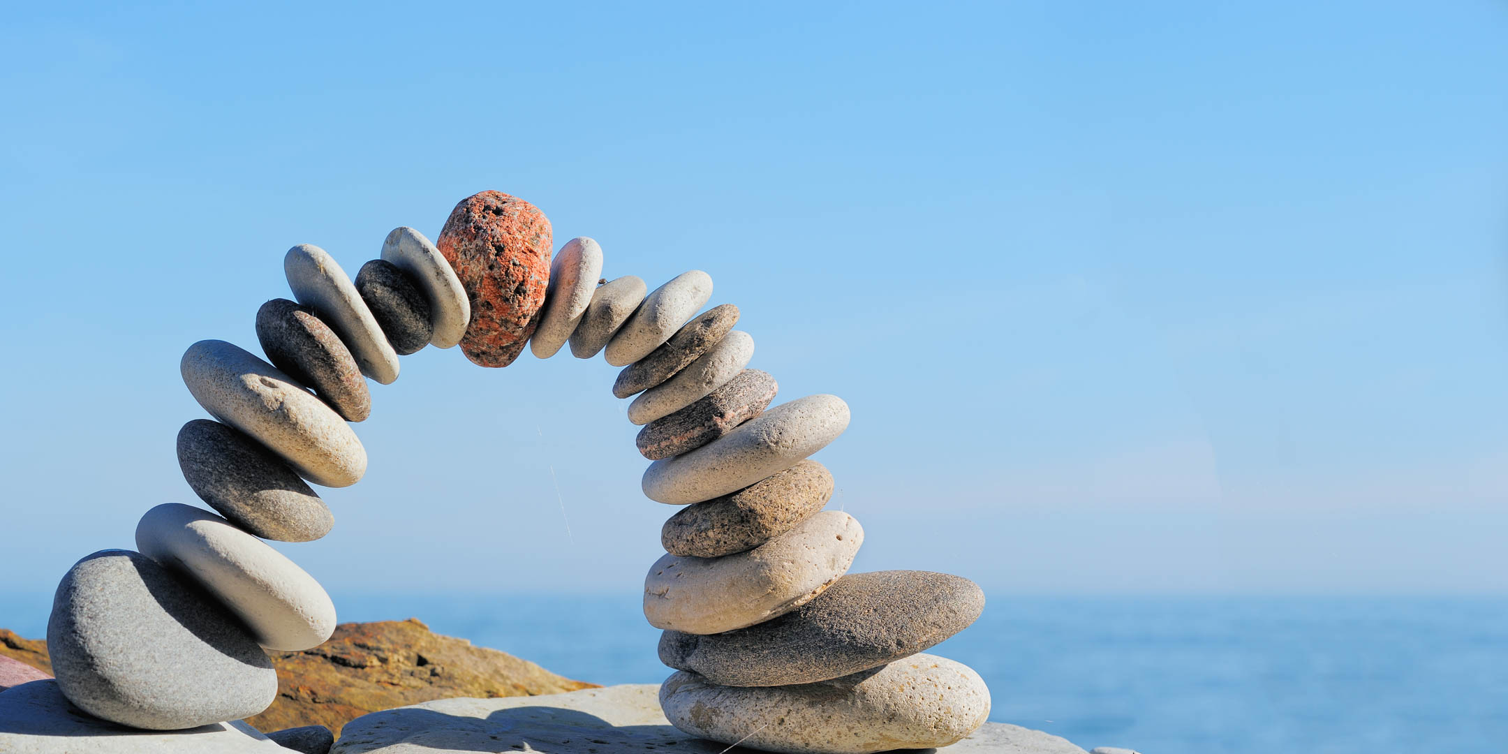 Mindfulness image - arch of pebbles with the blue sky and ocean behind